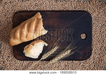 Broken bread and ears on a kitchen board against the background of wheat grains