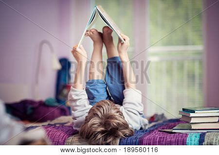 Little boy lying on bed playing with books.