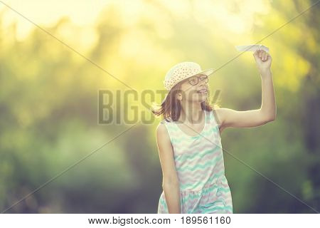 Cheerful pre-teen girl playing with paper plane on the park at sunrise. Girl with glasses and teeth braces.
