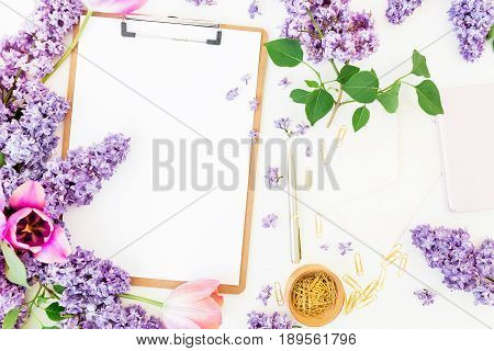 Freelancer or blogger workspace with clipboard, notebook, lilac and tulips on white background. Flat lay, top view. Beauty blog background.