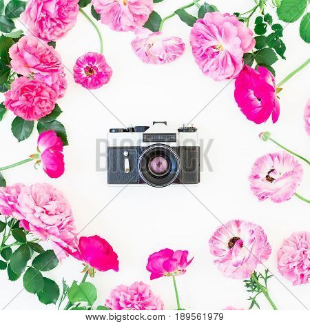 Old retro camera and roses, buds and leaves on white background. Flat lay, top view. Vintage background.