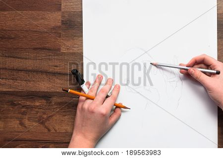 Painter's hands drawing sketch with pencil. Unrecognizable creative artist making new logo project. Drawing lessons, art school, young artist concept
