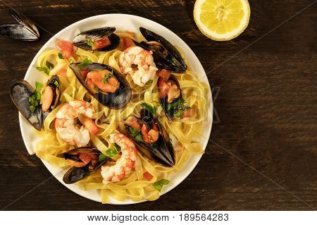 A photo of a ready to eat seafood pasta dish with mussels and shrimps, shot from above on a dark wooden rustic background texture, with a lemon half and some shells, with a place for text