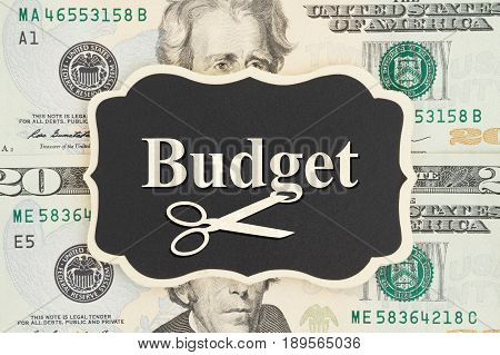 Budget text and scissors on chalkboard on USA twenty dollar bills