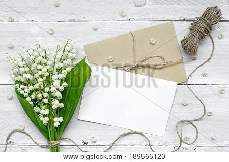blank white greeting card and envelope with white lily of the valley flowers bouquet and buds over white wooden background. mock up