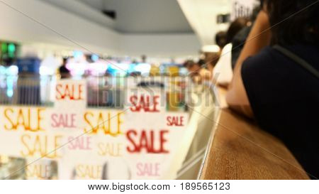 Blur background shopping mall has people see at sale banner Photo fucus select at on wooden handle on metal fence.
