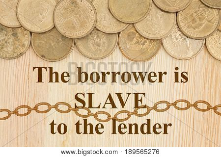The borrow is slave to the lender text with USA one dollar gold coins on a wood desk