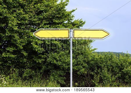 Empty yellow road signs pointing in opposite directions against green bushes and a blue sky symbol background with copy space for your own text
