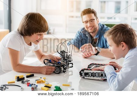 Happy smiling male children are standing near table and looking at each other. They playing robots. Teacher is watching them with smile