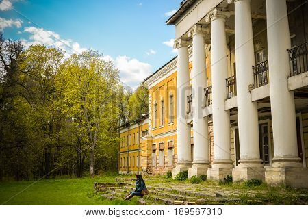 Moscow region, Russia - May 13, 2017 -Antique manor in village Sukhanovo. Abandoned mansion, trees, young pretty woman, sitting on ruined stairs. Nice landscape for calendars, posters, prints, design.