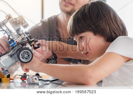 Active smiling boy is making robot. Attentive man helping him. They are sitting near table