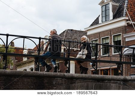 Monnickendam Netherlands - August 08 2016. Unidentified people sitting on bridge over the canal of traditional dutch village of Monnickendam. The town was founded by monks and it is a small fishing village today