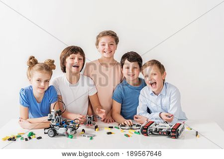 Happy children standing near table and looking at camera with bright smile. Robots are on countertop. Isolated