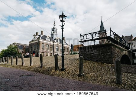 Monnickendam Netherlands - August 08 2016. Street view with old traditional houses and bridge over canal in the dutch village of Monnickendam. The town was founded by monks and it is a small fishing village today