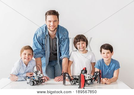 Happy adult man is among children. They inclining on countertop and looking at camera with wide smile. Portrait. Isolated