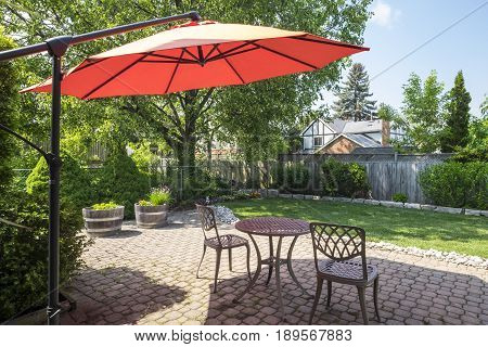 Backyard Garden with Bright Orange Cantilever Umbrella and Bistro Set