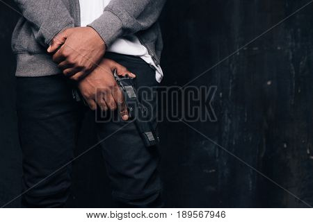 Unrecognizable armed black criminal man studio shoot. Gangster guy with gun in hand on dark background with free space. Outlaw, ghetto, murderer, robbery concept
