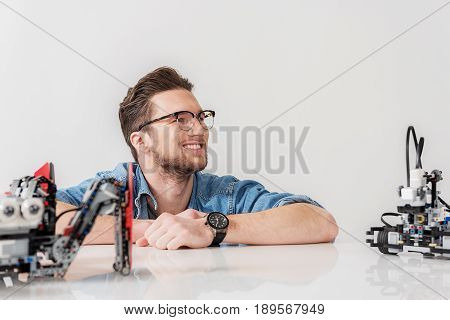 Merry adult man is squatting behind table and looking up with smile. Robots are on countertop