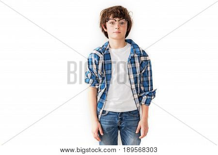 Disheveled boy wearing glasses is looking at camera with surprise. Portrait. Isolated. Copy space