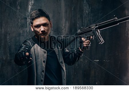 Tattooed face guy with sniper rifle pointing. Armed asian killer man with weapon and tattoo on dark background. Outlaw, ghetto, murderer, contract murder, robbery concept