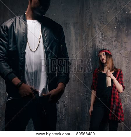 Criminal teenagers on dark background. Guy with gun and girl with alcohol. Gang members lifestyle