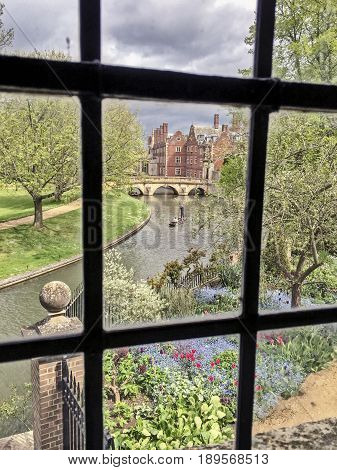 A view of the River Cam with a punt being poled along the river from the Wren Library in Trinity College. The library is part of Cambridge University.