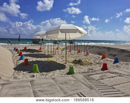 A deisgnated playground area on a portionof Miami Beach includes sand buckets shovels and umbrellas in a protected area.