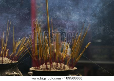 A ceremonial urn filled with smoking incense sticks. This display was in a Buddhist pagoda in Vietnam. The woman in the background is obscured by the swirling smoke.