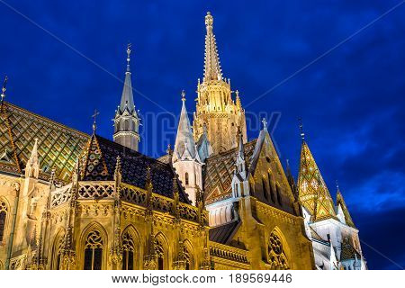 View of the Matthias Church during blue hour, roman catholic church located in Budapest, Hungary inside Fisherman's Bastion at the heart of Buda's Castle.