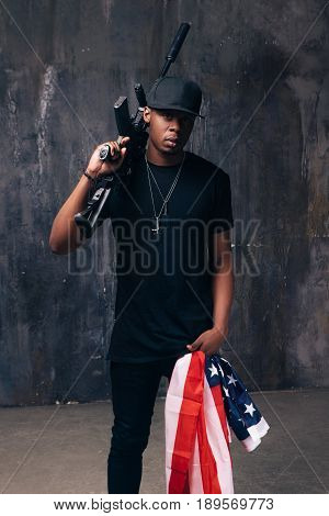 Armed confident black man with american flag and weapon stay on dark background. Gangster, patriotism, social problem, immigration, us citizenship, armed strike, bandit groups concept