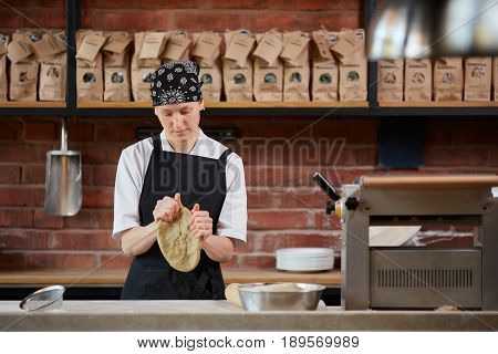 Young woman in uniform rolling a dough in a kitchen of cafe. Making pasta. Making pasta in restaurant. Woman kneading dough in kitchen