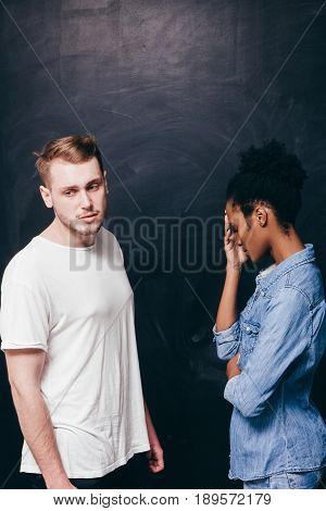 Young interracial couple in quarrel. Relationship problem, sadness , divorce and despair. Disappointed man and woman, serious conversation, conflict, quarrel and breakup concept.
