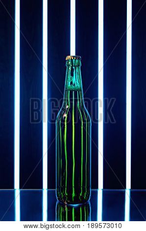 green beer bottle on dark background with bright bands of light and specular reflection
