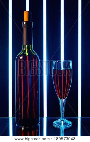 red wine bottle with glass on dark background with bright vertical strips of light on the table mirrored