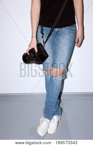 Unrecognizable female photographer and photocamera on belt. Casual girl in damaged fashionable jeans with professional equipment in white room