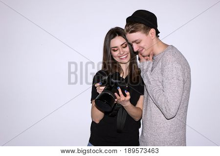 Two hipsters enjoy with digital camera on white background. Female photographer show to male model photos. Woman and man is happy. Friendship of sexes, lifestyle, leisure, hobby concept