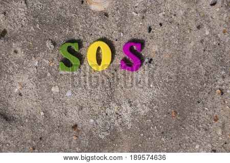 word sos from wooden letters on a sandy beach a top view