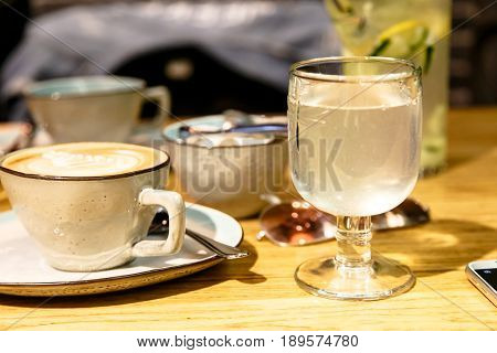 A Cup Of Coffee And A Glass Of Water Or Lemonade Stand On The Table.