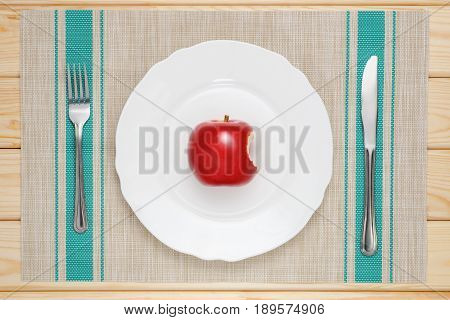 bitten red Apple on a white plate on the table with a knife and fork