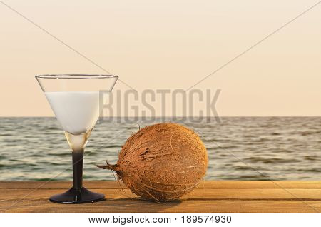 Fresh coconut cocktail on a tropical beach in sunset time on the wooden table a vacation in the summer. vintage color styles