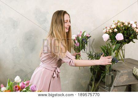 Florist choose flower for bouquet. Decorator workshop. Woman in flower shop workplace , assembling spring pink composition