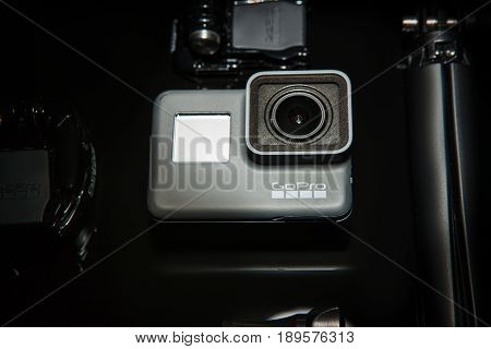 Kharkov, Ukraine - April 13, 2017: GoPro HERO 5 action camera with tripod closeup on black background. Compact gadget waterproof, support 4k video and is often used in extreme photography