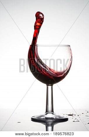 Pure wineglass with wave of brightly red wine on white background.