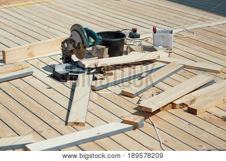Cutting wooden floor by electric saw in work place
