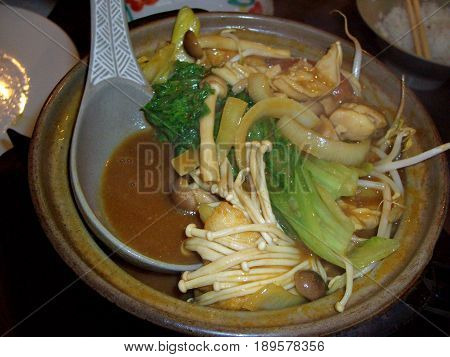 Mix vegetable stew in a pot A pot of stewed mixed vegetables in a pot with serving spoon