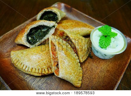 Mediterranean empanada stuffed with vegetables Empanadas stuffed with healthy vegetables served on a wooden plate, and dipping with basil leaves