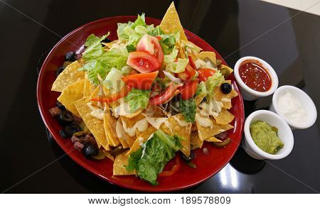 Nachos and three dips Nachos topped with tomatoes, green lettuce, olives and bacon bits in a round red plate, served with small bowls of ketchup, mayonnaise and avocado dip.