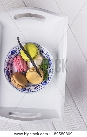 Colored macaroons, mint and vanilla bean on a white wooden background