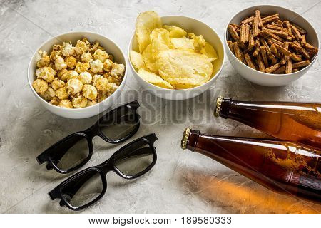 home party with TV watching, snacks, pop corn, chips and bread crumbs and beer on stone background