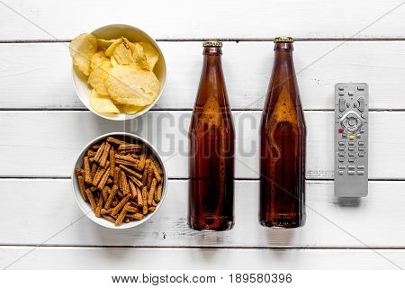 home party with TV watching, snacks, chips and bread crumbs and beer on white background top view